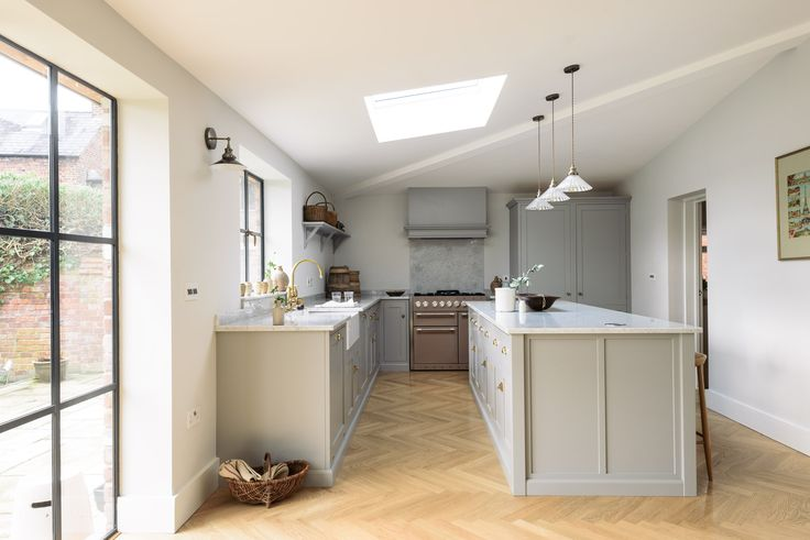 deVOL's Chester Kitchen features soft grey cupboards, parquet flooring, crittall style windows and luxurious Carrara marble worktops