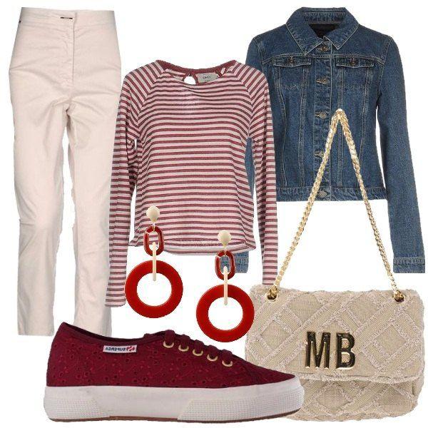 Outfit composto da pantaloni in tela a vita alta, t-shirt in jersey a righe, giubbotto di jeans lavaggio scuro, sneakers in pizzo con logo, borsa a spalla canvas tinta unita con logo e orecchi in metallo bicolore.