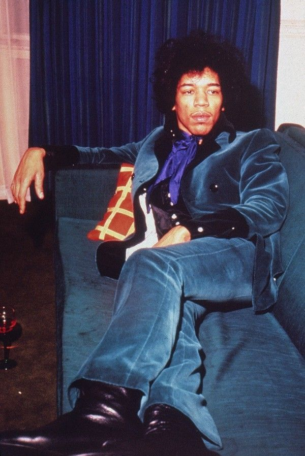 jimi hendrix in his velvet suit that matches the furniture