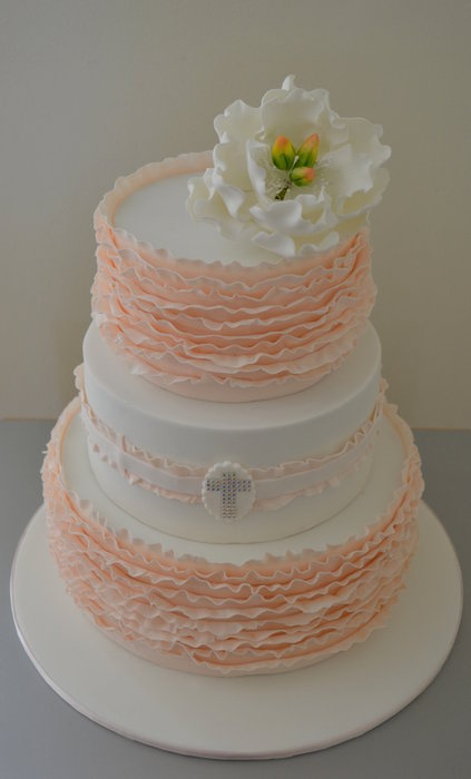 3-tier white Christening #cake with delicate peach ruffles, a small jeweled cross, and a large fondant flower. Simply gorgeous!