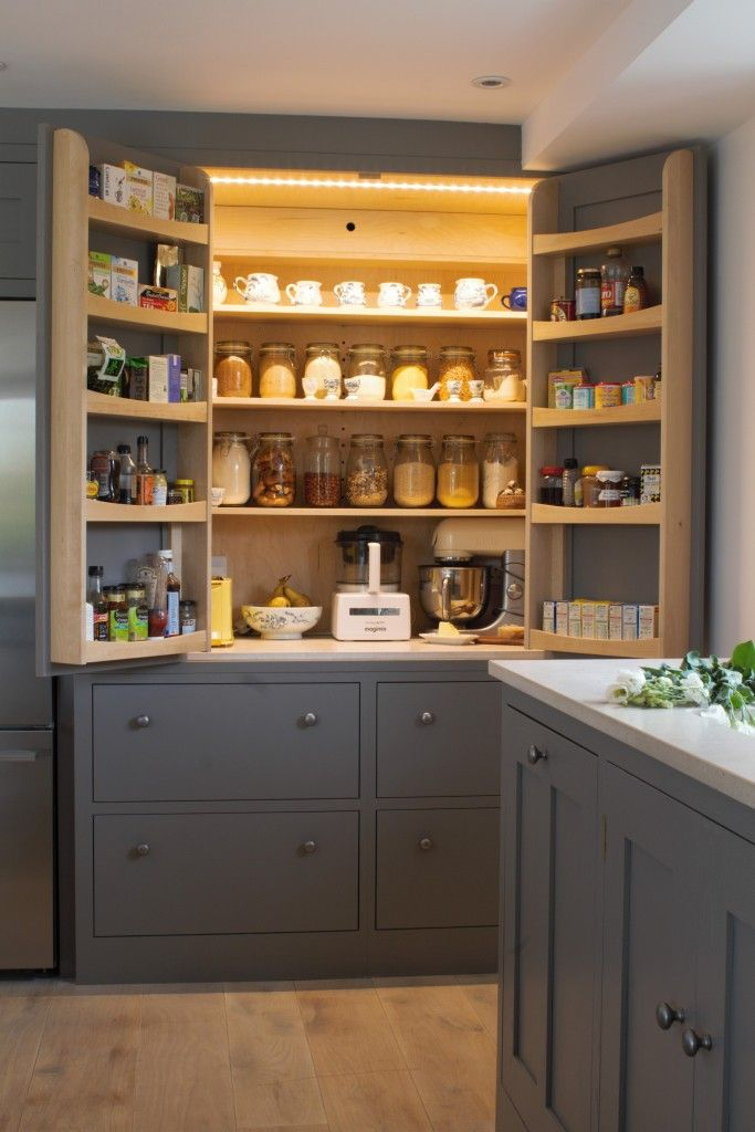 An open LED lit larder cupboard with amble storage and efficient ventilation painted in Farrow & Ball Mole's Breath. The bottom shelf is a cold shelf with built in wall ventilation with the drawers below also used as cold storage for vegetables. Bringing old traditions into a a modern kitchen.