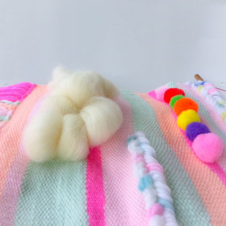 Weaving clouds with colorful Pom poms are the best weaving wall hanging for the nursery decor.