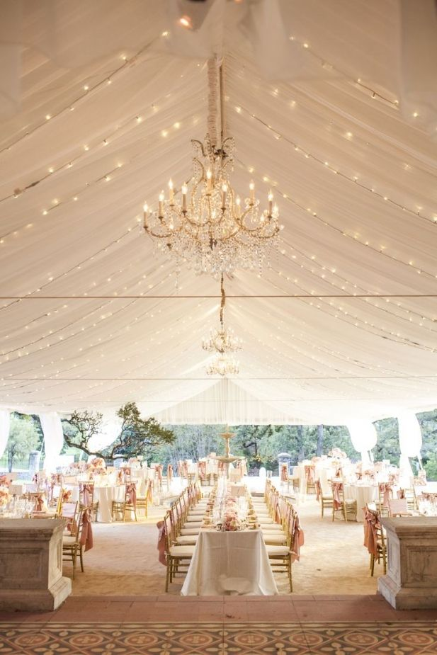 Truly elegant outdoor reception with twinkle lights, chandeliers, gold color chiavari chairs...