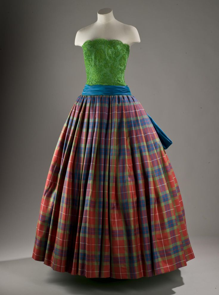 Woman's ball dress with a leaf green lace bodice, turquoise blue sash and bow, and tartan silk skirt: English, London, by Hardy Amies, 1989