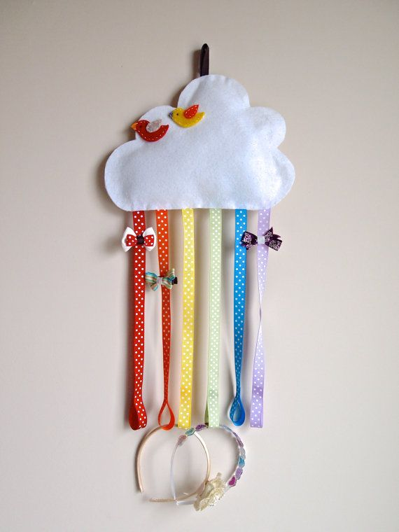 Store your hair clips and hairbands in one place with this whimsical rainbow organizer! This is also a perfect addition to a cloud or rainbow themed nursery. Ive handmade the cloud using glittery white felt and battling, and hand-stitched the felt birds. There are six polka dotted rainbow ribbons (12.5 inches long) to hold all your hair bows. Each ribbon has a loop at the bottom to hold hairbands. The cloud is 11 inches at its widest and 8 inches at its highest. Hairbands and hair clips in…