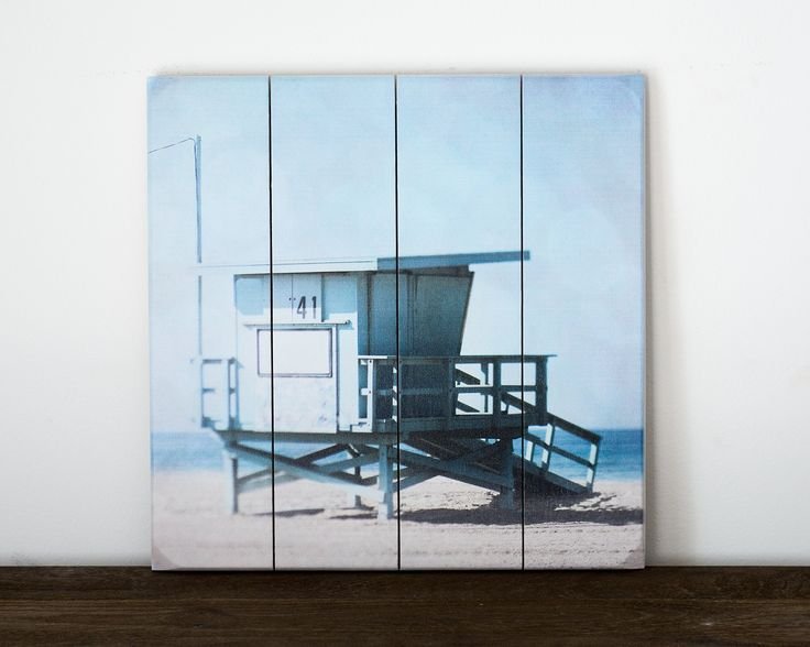Lifeguard Stand Picture 13x13 inch Ready to Hang Square Wood Plank Art. This coastal art features a photograph of a blue lifeguard tower on a sandy beach overlooking the ocean. This 113x13 inch wooden plank art is ready to hang with hardware installed on back. Colors may vary slightly due to differences in monitors. They are printed by a professional lab and packaged in sturdy moisture resistant packaging to ensure they arrive in perfect condition. Modern nature wall decor for your shabby...