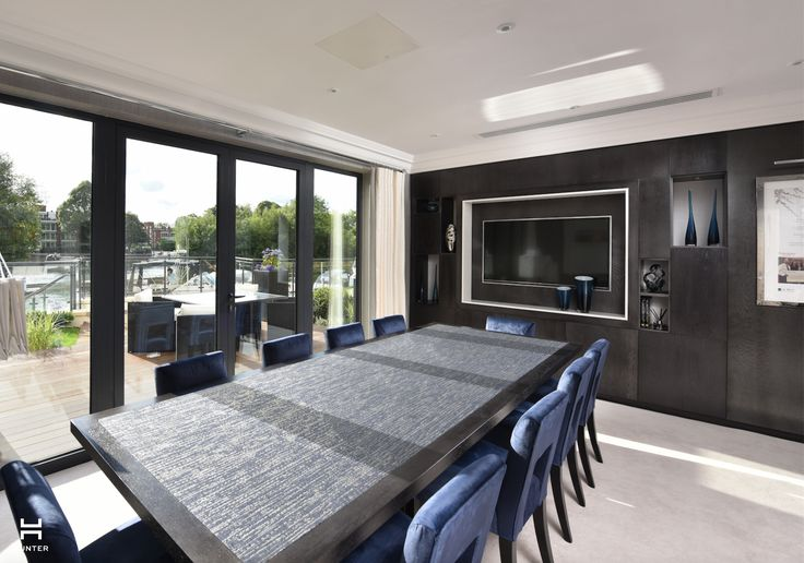 Taplow Riverside Marketing Suite www.hunter-design.co.uk  Bespoke joinery and meeting room table in dark timber with inset fabric detail.  Splash of blue in the chair upholstery and accessories.