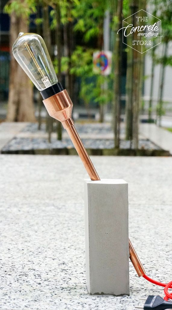 An edison tube bulb perched on a polished copper tube with a casted concrete base, as a table side lamp with internal socket and 1.4m/5ft red fabric wire cord. Dimensions: 100mm x 100mm x 300mm (450mm copper pipe)  Please indicate: Socket Type: USA (Rounded) / UK (Flat) Edison bulb Type Fabric Cord Color  Materials used: Copper pipe, Concrete, E27 electrical mount , 1.4m red fabric cable with ceiling electrical connection; Bulb: - E27 edison bulbs Notes: This is a made to order item, so…