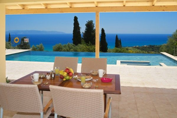 Wide patio doors form a seamless extension through to the shady veranda that runs the full width of the house and beyond to the view over the pool and to the Greek island of Zante on the horizon.