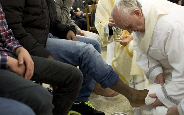 Pope Francis washes the foot of a prison inmate during Holy Thursday Mass in 2013 (CNS)