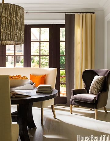 "In the dining room of an Atlanta, Georgia, house, designer Kay Douglass used a palette of dark brown with cream and orange accents. Curved banquettes that seat three people each were custom-made to conform to the curve of the table. ""It makes the dining experience a little bit different and definitely creates intimacy,"" Douglass says. Ebony dining table and Noella chair from South of Market. Drum light customized with Galbraith & paul Fern fabric."