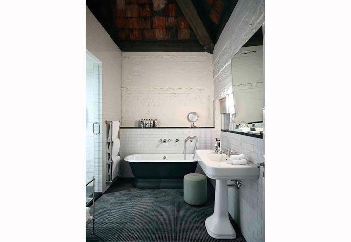Bagno con muratura originale e piastrelle, vasca da bagno e pavimento in mosaico