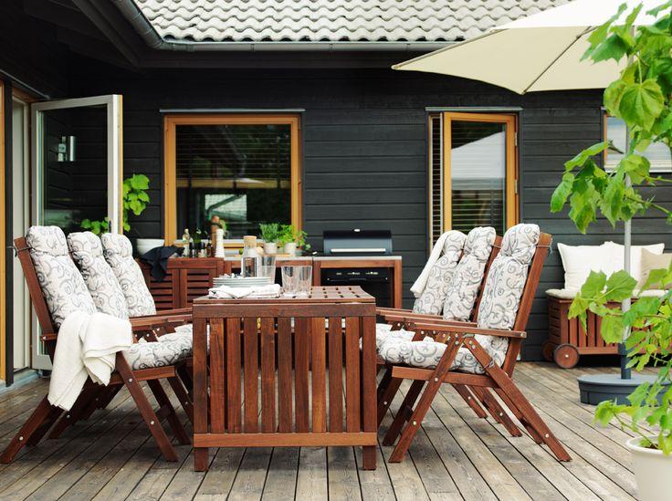Terrasse avec six fauteuils inclinables avec coussin assise autour d'une table en bois et barbecue noir en arrière-plan.