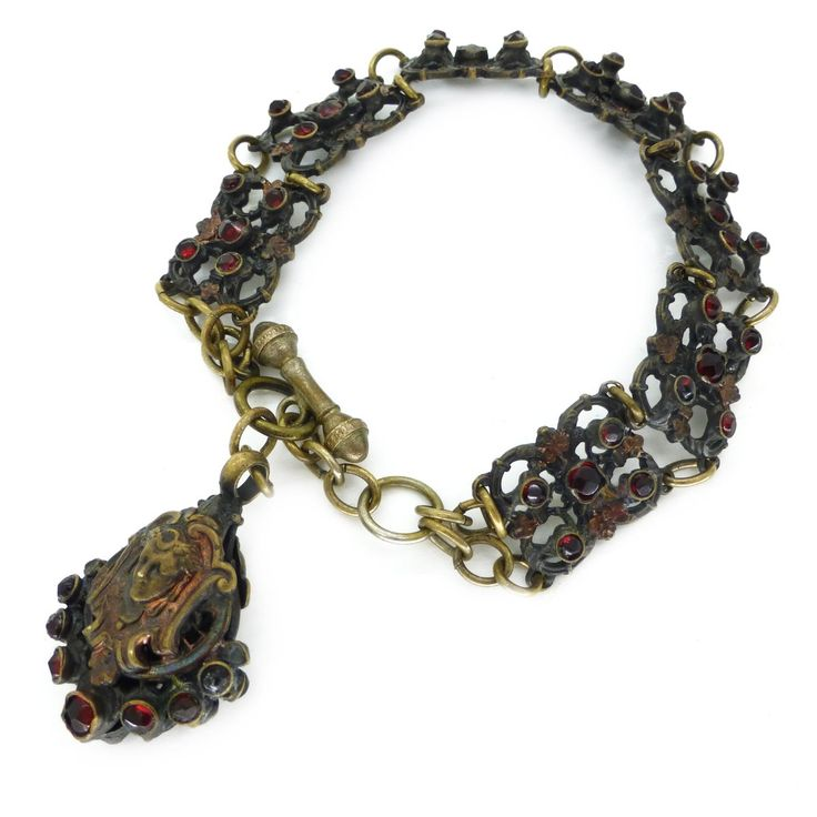 ANTIQUE AUSTRO HUNGARIAN GARNET GLASS FILIGREE FIGURAL FACE CHARM PANEL BRACELET | Clarice Jewellery