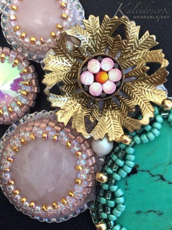 LUCREZIA floreale in rilievo, perline ricamo verde turchese, quarzo rosa e collana doro. Questo unico nel suo genere, arte da indossare collare ha un vibe primavera femminile, fresco. Cinque, grande autentico verde tibetano turchese cabochon sono racchiusi in un cordone di tessuto, lunetta smerlato e si unì con cabochon di quarzo rosa, Swarovski rivolis e fiori dellannata doro impostato con antichi mosaici floreali micro per formare un collare stile funky asimmetrica.  Tutti i branelli del…