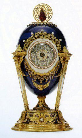 Il quadrante dell'orologio, incorniciato con una fila di perle fissate tra bordi di lucido oro rosso, è posto in un'area ovale del guscio, smaltata in bianco opaco e contornata nella parte superiore da un arco di rami d'alloro baccati su una griglia decorata con diamanti e perle e nella parte inferiore da una frangia traforata e decorata con diamanti, alla quale sono appese nappe e festoni di frutta. I numeri arabi decorati con diamanti sono posti al centro di aree circolari smaltate in…