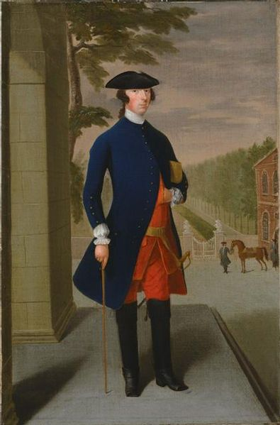 Joseph Leeson of Ireland, later 1st Earl of Milltown, wears a narrow-sleeved blue coat lined in red with a red waistcoat and breeches. He wears a tricorne and tall black riding boots, 1730s.