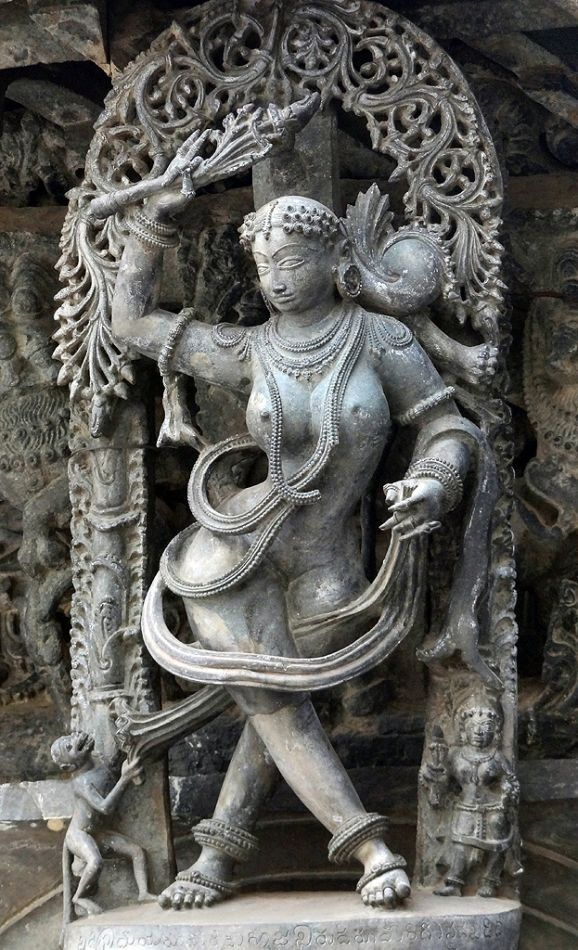 Belur Chennakeshava Temple-Here, a monkey is teasing the lady by pulling her sari. The lady is trying to shoo the monkey off by holding a tendril in her hand.