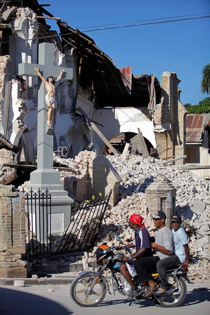 Residents pass a damaged church in Port-au-Prince after a devastating earthquake hit Haiti
