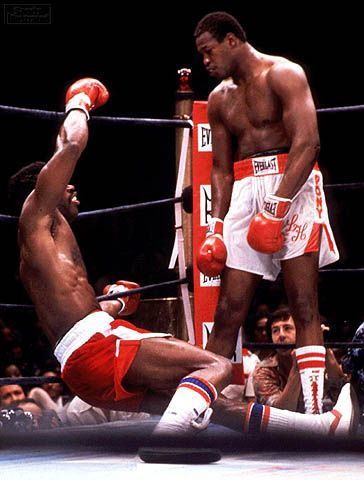 Larry Holmes knocks down Mike Weaver during an amazing, breathless brawl! Holmes would finish Weaver, who was leading on the scorecards, by KO in the 13th.