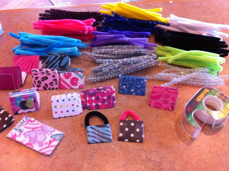 Girl Scout Swap Purses...cut scrap book paper + cut pipe cleaners (into 1/3 for the right size handles + tape...just add a safety pin. you can also add jewel embellishments! very little cost (already had paper & pipe cleaners; only cost was pins and jewel stickers from Michaels).