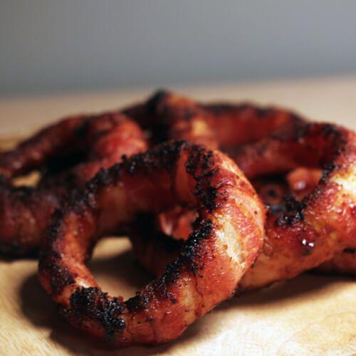 Met dit BBQ recept voor in bacon gewikkelde uienringen heb je alle BBQ smaken die je je maar kunt wensen in één gerecht. Een echte aanrader!