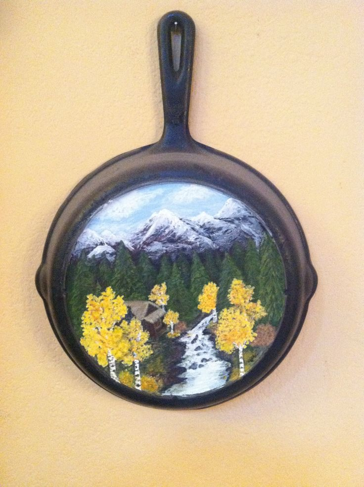 A cabin in the woods painted on a cast iron skillet.