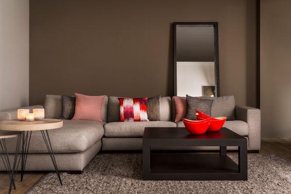 In dit interieur hebben we gekozen voor een grote hoekzetel met een natuurlijke linnen look. De rode accenten zorgen voor een knus en gezellig gevoel. Perfect voor het najaar!
