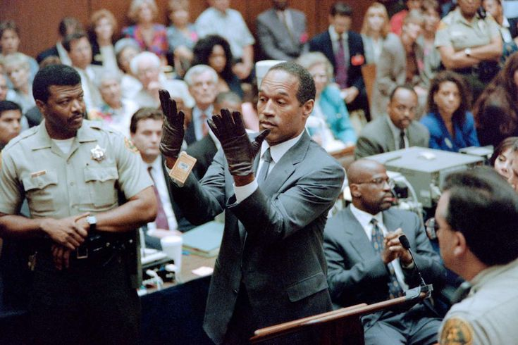 O.J. Simpson looks at a new pair of Aris extra-large gloves which the prosecutors had him put on for... - Vince Bucci/AFP/Getty Images