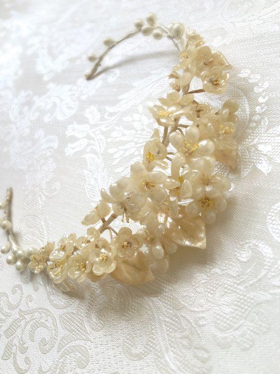Ein schönes Beispiel für einen frühen 1930er Jahre Art-Deco-Wachs Tiara.  Orangenblüten Blumen in cremigen Tönen mit blass Zitrone Staubblätter und durchsetzt mit cremigen Wachs Blättern, die einen fast irisierenden Glanz haben. Ein Cluster von Elfenbein Knospen decken die Arme der Band, der in Elfenbein satin Faden umwickelt ist.  Alle Blumen sind vorhanden; Es scheint nur eine Knospe fehlten im unteren Bereich des Armes, obwohl das nicht merkt, wenn wegen es ist getragen.  Ich denke…