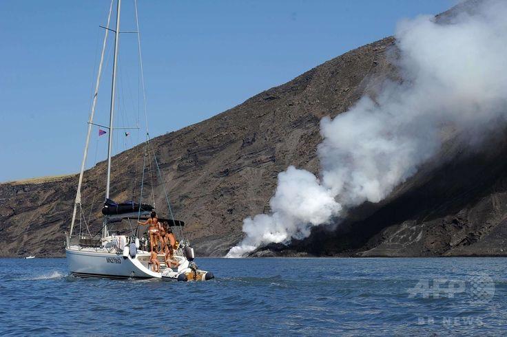 イタリア南部のシチリア(Sicily)島沖にあるストロンボリ(Stromboli)島で、火山から噴出した溶岩が海に流れ込む様子を見学するボート(2014年8月9日撮影)。(c)AFP/GIOVANNI ISOLINO