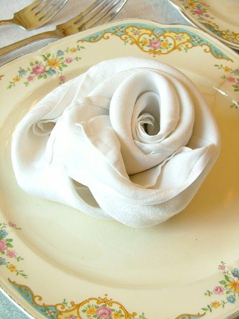 Rose shaped napkin folding - to make this flower napkin shape:  fold the napkin in a triangle, then roll it up from the pointed end & then from one of the ends, start rolling into a rose shape