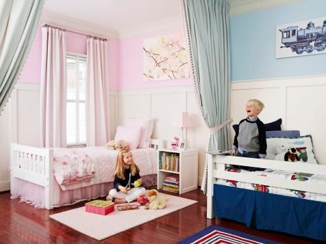 """Genevieve and Crawford's shared bedroom gets its character from pom-pom-trimmed divider curtains and molding that stretches almost 6 feet high. """"I saw similar paneling in a catalog and loved the look,"""" says Dana. The trend-proof Pottery Barn Kids beds don't match but seem like a set because they have the same simple lines and color."""