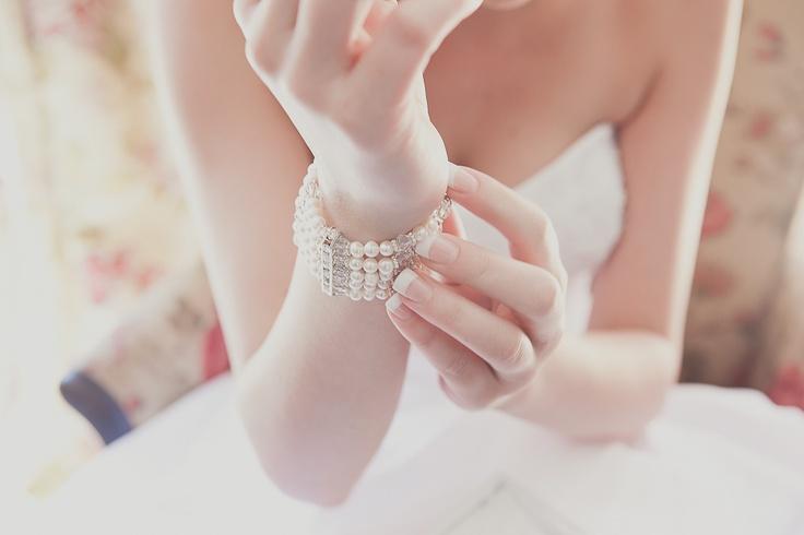 Bride putting on bracelet taken by Veronique-Photography