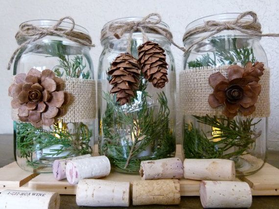 Make the center one - battery tea light/epsom salt in bottom of jar (to look like snow).  Tie jar/pinecones with ribbons not twine, with a rose & pine laying alongside. Possibly on slice of tree trunk? Consider frosting jar or using snifters. Dip rims in glue & glitter to frost