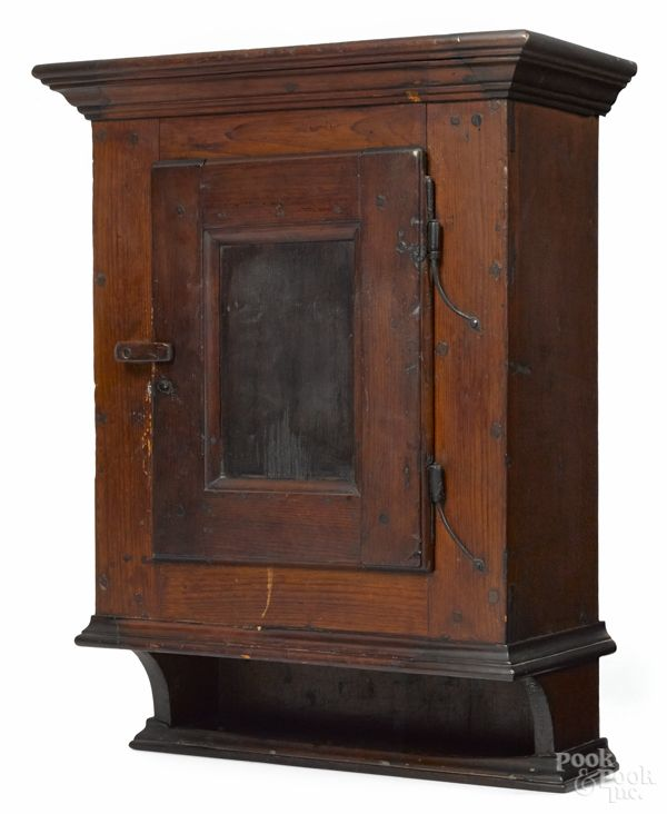 """Lancaster County, Pennsylvania pine hanging cupboard, late 18th c., having a single door with a sunken panel and rattail hinges, 29"""" h., 20 1/2"""" w., 9 1/2"""" d. Estimate: $2,000-3,000"""
