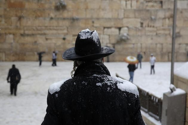 A man stands in front of the Western Wall as snow falls in Jerusalem's Old City December 12, 2013.
