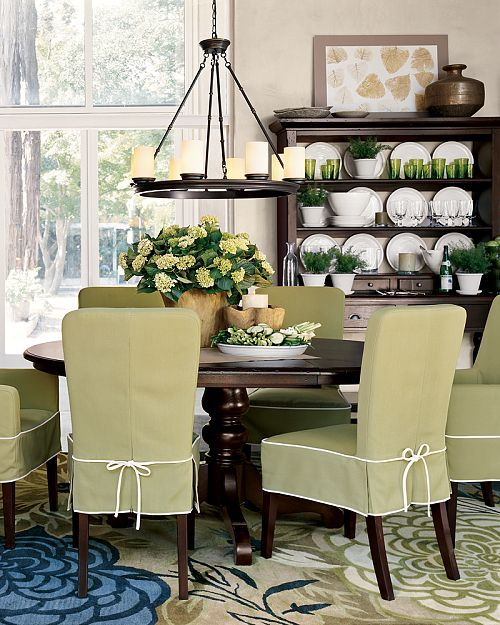 Lovely dining room. Love the green slip covers. Great rug and light fixture.