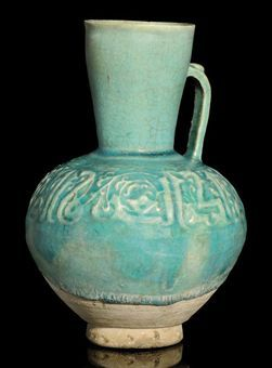 A TURQUOISE GLAZED MOULDED POTTERY JUG, IRAN, 13TH CENTURY