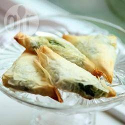 Греческие пирожки со шпинатом и фетой (Спанакопита)-Получается: 20 штук 20 листов теста фило, разморозить 500 г шпината (или 250 г мороженого) 150 г феты 1 луковица 2 ст.л. оливкового масла 2 яйца 4 ст.л. муки соль и перец 50 г сливочного масла, растопленного
