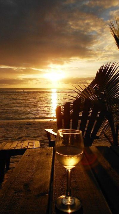 An Adirondack chair, a nice glass of apple juice! ha, the waves, and Sunset