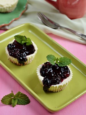 Small cheesecake-style treats topped with sweet blueberry pie filling, sure to be a hit at your next picnic.