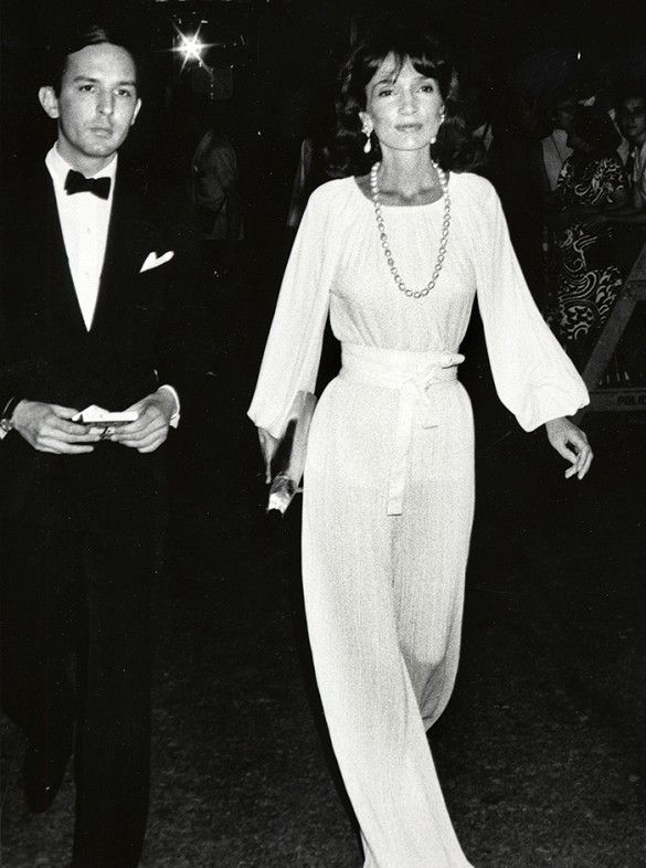 Lee Radziwill wears a white belted jumpsuit with a large pearl necklace, statement earrings, and a metallic clutch