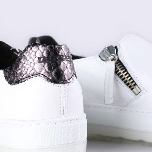 Take the road less travelled with these unique flatform sneakers from Diesel, and bring an air of elegance to traditional street style. Features include a rubber low platform sole and a white leather upper with zip detailing on either side and a metallic faux skin heel panel. Wear them with some simple black leggings and a statement track top to complete the look.   Shop now online and in store #loveshoes #shoes #sneakers #details #style #fashion #instagood