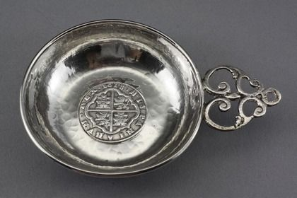 "A Spanish silver porringer, inset with a Spanish eight reale coin (one of the famous ""pieces of eight"") dated 1618, the reign of Philip III (1578-1621). The porringer is hand beaten, with the individual hammer marks clearly visible, creating an attractive pattern. The rim is folded over, and the cast flat handle has a scrolling design. The handle is quite crudely cast, we believe a sign of age. We have dated the porringer 17th century to co-incide with the date of the coin, but it could be…"