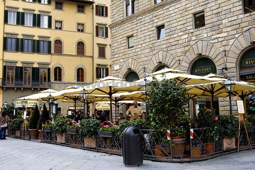 Stock photo of attractive outdoor cafe with umbrellas outside old stone building in Piazza della Signoria in Florence, Italy. Description from acclaimimages.com. I searched for this on bing.com/images