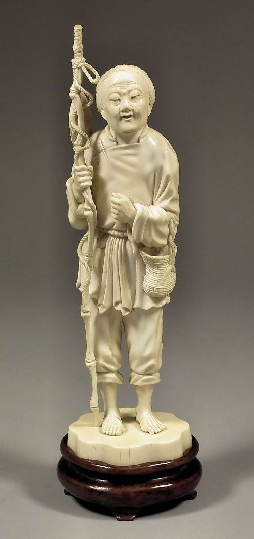 A Japanese (Tokyo School) carved ivory figure of an elderly fisherman carrying a bamboo fishing pole, on shaped oval base 9ins (228mm) high (Meiji period - unsigned) with hardwood stand