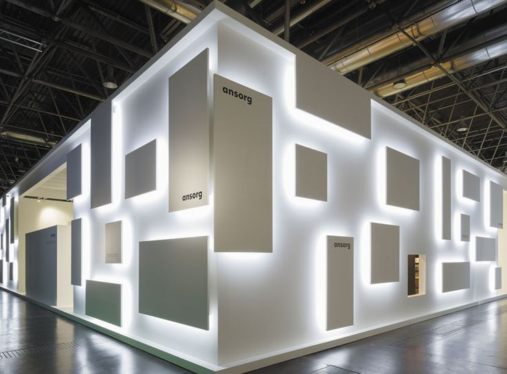 Comprised of little more than white laminate dotted with various square panels, Ansorg GmbH's hidden light fixtures beneath simple panels create a striking piece of shadow play! #eventprofs #booths #exhibits