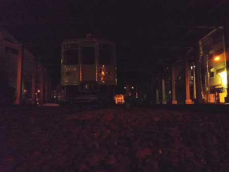 駅から続く、ビルの下の線路。踏切の間際に、列車が停まっている。灯りを落とされた車両は、ただ静かに。[2011/8 瓦町駅 高松琴平電気鉄道琴平線 夜間滞泊列車(1300形)]© 2010 風旅記(M.M.) 風旅記以外への転載はできません...