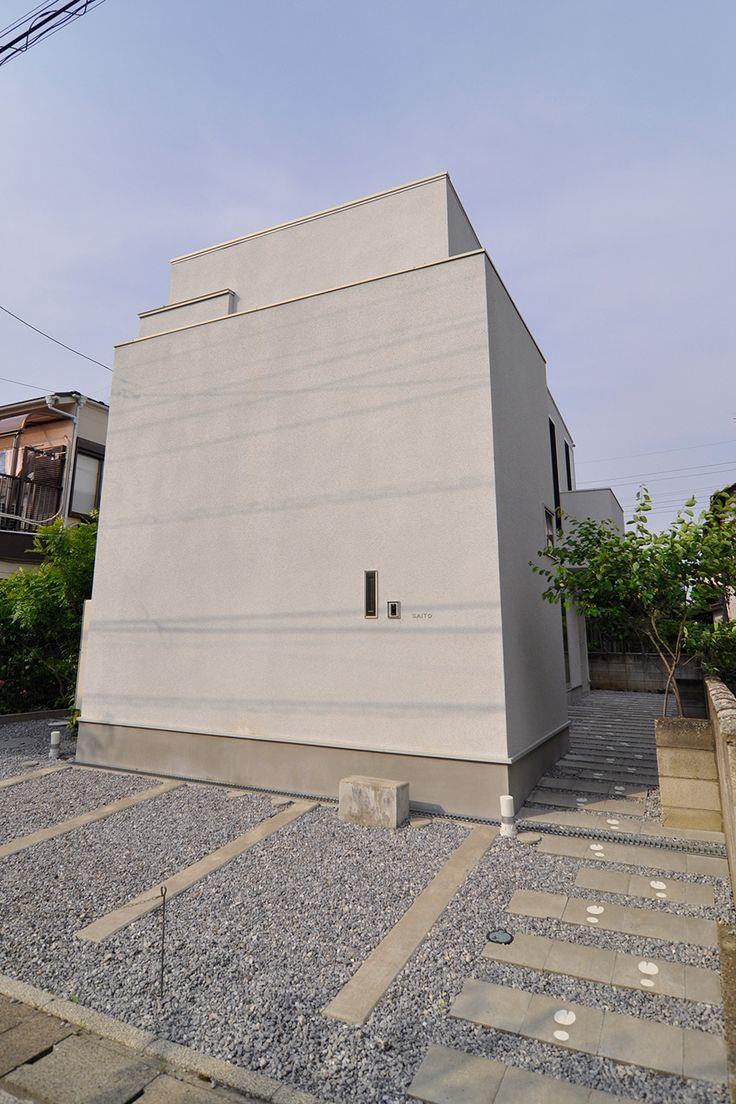 中の明るく大胆な設計が想像できない、シンプルな箱形の外観。手前の壁にポツンと開いているのはポスト。